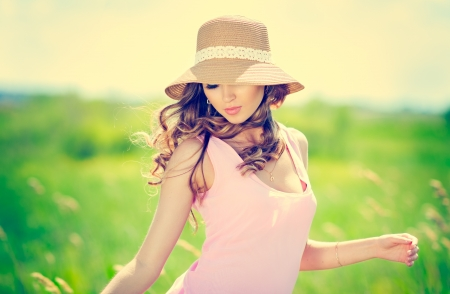 Beautiful happy woman in hat on summer meadow photo