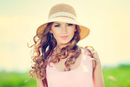 Beautiful happy woman in hat on summer meadow