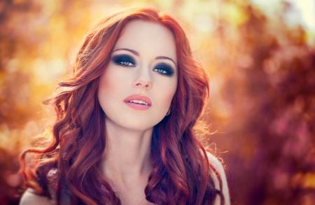smoky eyes: All'aperto ritratto di una bella donna con i capelli rossi e gli occhi fumoso trucco