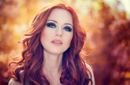 Outdoors portrait of beautiful woman with red hair and smoky eyes makeup photo