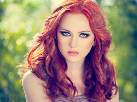 summer portrait of a beautiful girl with long curly red hair Imagens