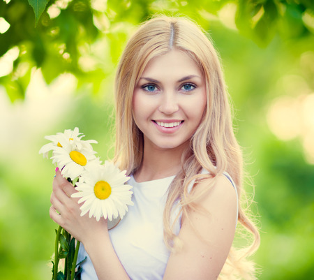 Beautiful happy smiling young woman with daisies Imagens