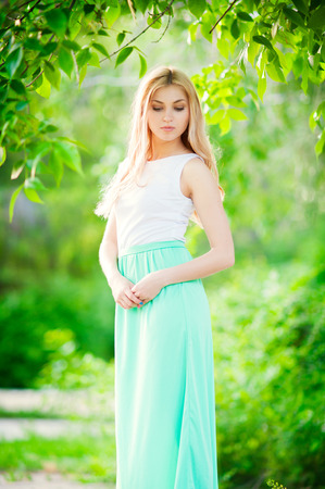 Beautiful Young happy Woman Outdoors in a long dress looking down Imagens