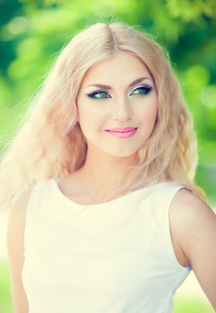 beautiful woman with bright makeup and blonde long hair photo
