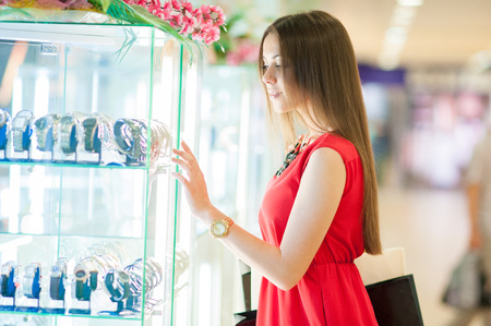 Beautiful smiling girl in a red dress with long hair shopping, looking in the shop window