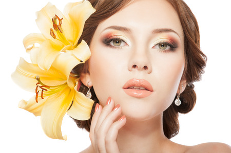 Beautiful woman with hairstyle, bright makeup, manicure  With lily flowers