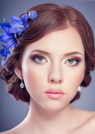 Beautiful woman with hairstyle, bright makeup, With bells flowers Imagens