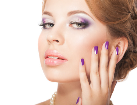 Beautiful woman face with bright makeup and manicure Imagens