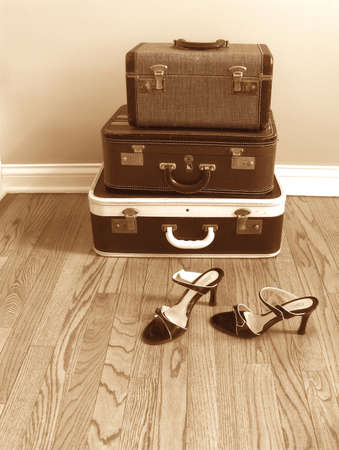 vintage suitcases with womens shoes, sepia