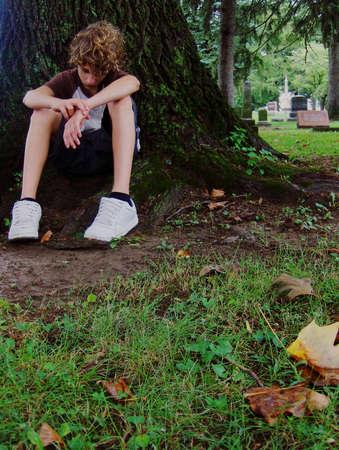 Tiener jongen vergadering onder boom depressief gevoel Stockfoto - 1552136