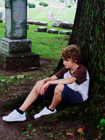 sad young teen sitting under a tree at cemetary