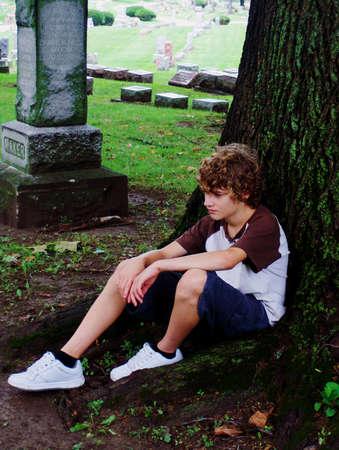 triest jonge tiener zitten onder een boom op het kerkhof Stockfoto