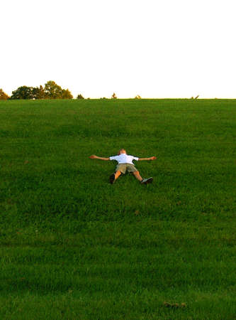 teen in snow angel position on grass hill