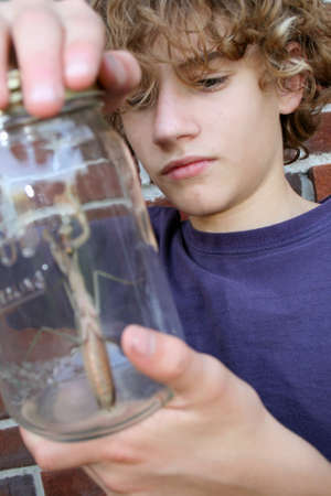 teen boy holding jar that contains a large bug