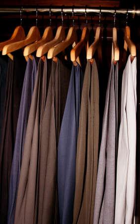 mens dress slacks hanging in a dark wood wardrobe closet Stock Photo