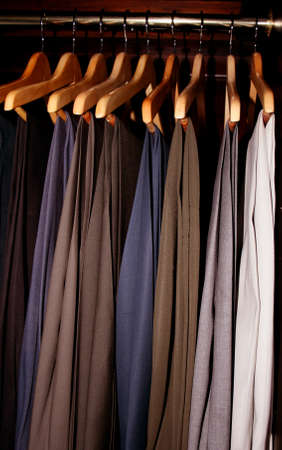 mens dress slacks hanging in a dark wood wardrobe closet Imagens