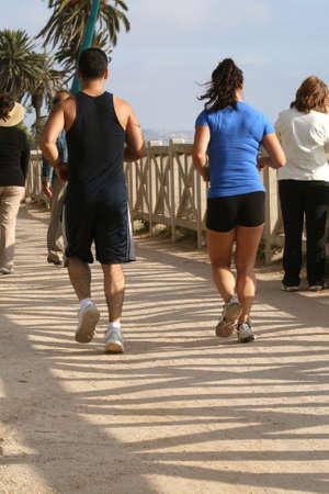 Joggers along path in California beach area