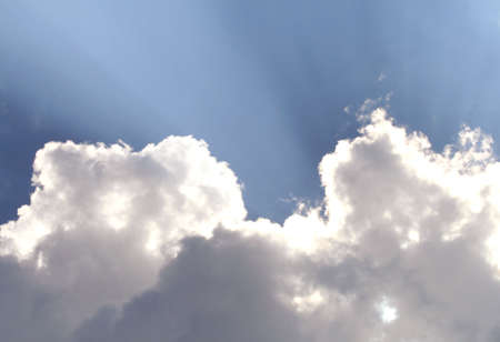 white puffy clouds backlit by sun 스톡 콘텐츠