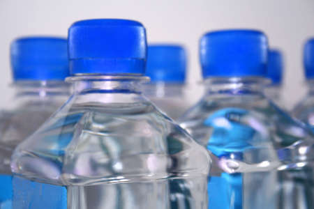 group of clear, square water bottles with blue lids