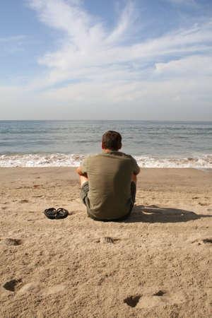 eenzame man zit op het strand kijken naar de golven
