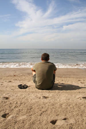 solitary man sitting on beach watching the waves Stock Photo