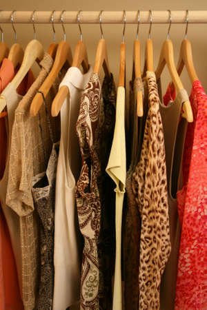 pretty blouses on wooden hangers in wardrobe closet Stockfoto