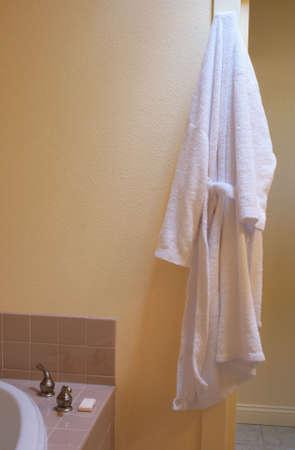 white bathrobe hanging in sunny bathroom