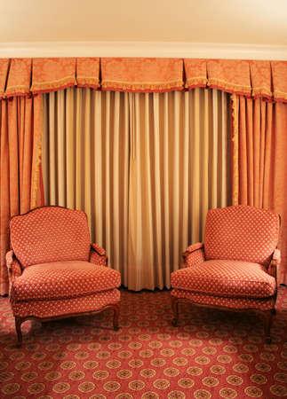 fancy stuffy chairs in front of fancy stuffy draperies