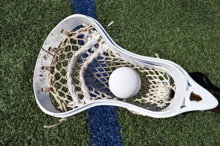 Lacrosse head with ball on blue line on turf