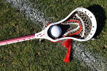 Lacrosse stick with ball on grass and white line