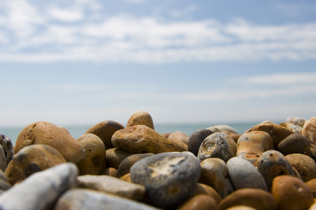 low angles: beach background of pebbles, sky and clouds Stock Photo