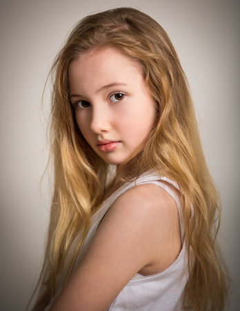 Portrait of a beautiful young girl with long blond hair and bare shoulders isolated against a grey background photo