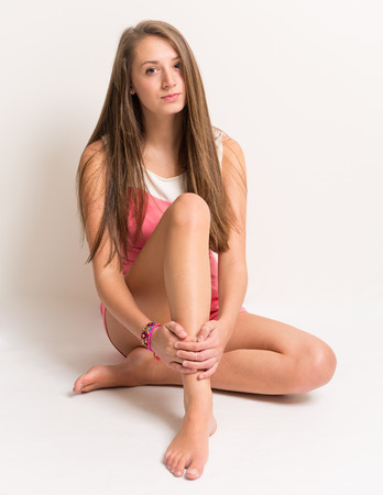 nude girl young: Studio portrait of a beautiful young teenage girl sitting on the groung hands crossed around her shin