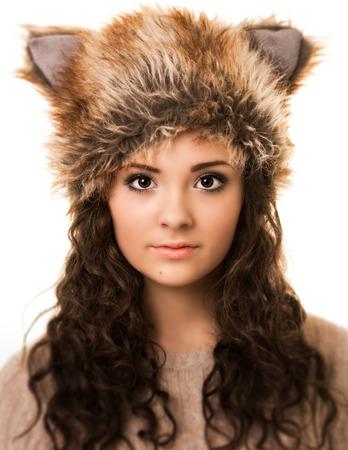 ojos cafes: Retrato de una hermosa mujer morena con el pelo rizado y ojos marrones que llevaba un sombrero divertido zorro aislado contra un fondo blanco