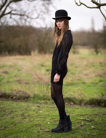 Portrait of a beautiful young woman wearing a black dress, nylons, boots and a bowler hat standing in a country farm field, hair blowing in the wind. photo
