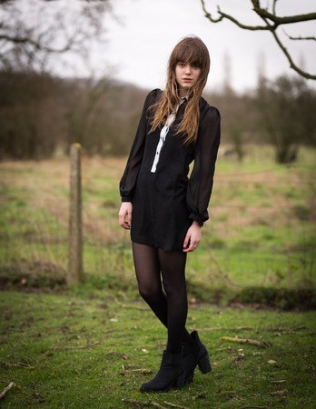 Portrait of a beautiful young woman wearing a black dress, nylons and boots standing in a country farm field, hair blowing in the wind. photo