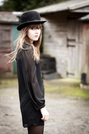 Portrait of a beautiful victorian style woman wearing a bowler hat and black dress standing in front of country farm stables photo