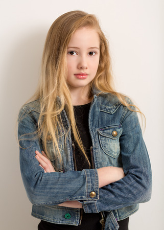 bata blanca: Retrato de una chica rubia muy joven en una chaqueta de mezclilla con los brazos cruzados aislados sobre un fondo gris claro Foto de archivo