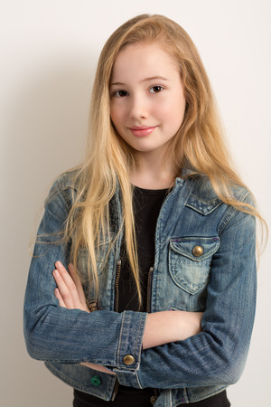 Portrait of a pretty young blond girl in a denim jacket with her arms crossed isolated against a light grey background Stock Photo