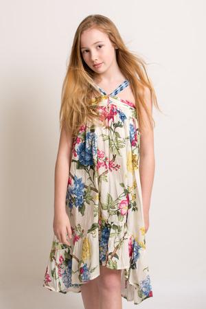 petite fille avec robe: Portrait d'une belle jeune fille blonde adolescente dans une robe d'�t� fleurie avec le vent dans ses cheveux isol� sur un fond gris clair Banque d'images