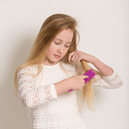 untangle: Portrait of a pretty young girl in a white dress brushing her long blond hair with a purple brush isolated against a light grey background Stock Photo