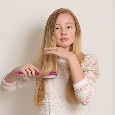 Portrait of a pretty young girl in a white dress brushing her long blond hair with a purple brush isolated against a light grey background Stock Photo
