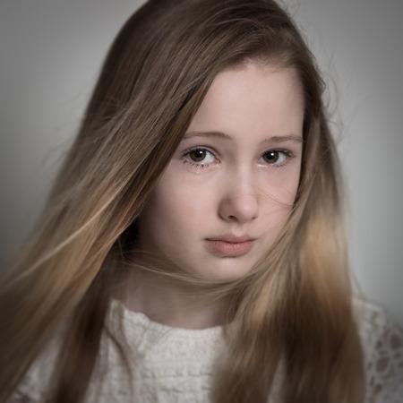 petite fille triste: Jeune blonde adolescente aux cheveux longs avec un visage triste, pleurs isol� sur un fond gris