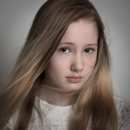 little blonde girl: Young blond teenage girl with long hair with a sad face, crying isolated against a grey background