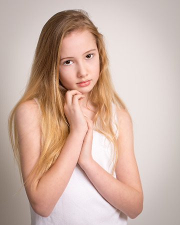Portrait of a beautiful young girl with long blond hair and bare shoulders isolated against a grey background Stock Photo
