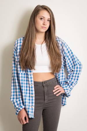 arrogant teen: Portrait of a beautiful teenage girl in a white top and blue shirt with long brown hair isolated against a light grey background wearing grey trousers Stock Photo
