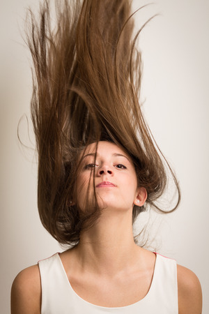 Portrait of a beautiful young woman flipping her hair up in the air making it look like it