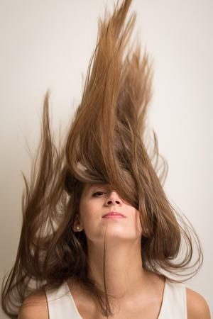 mujeres morenas: Retrato de una hermosa mujer joven volteando su pelo para arriba en el aire haciendo que parezca que Foto de archivo