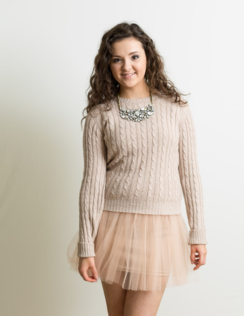 Portrait of a beautiful brunette woman with curly hair wearing a tutu like pink mini skirt against a whte background. Also wearing a necklace