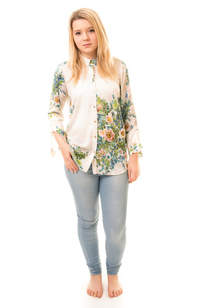 Portrait of a beautiful blond teenage girl wearing blue trousers, a flowery white shirt and bare feet isolated against a white background